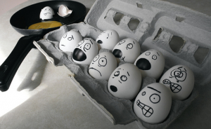 A dozen eggs with various stressful faces drawn on them, sit next to a hot frying pan.